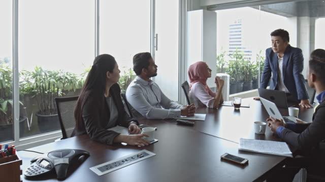 video von reifer geschäftsmann erklären mitarbeiter treffen schwenken - konferenztisch stock-videos und b-roll-filmmaterial