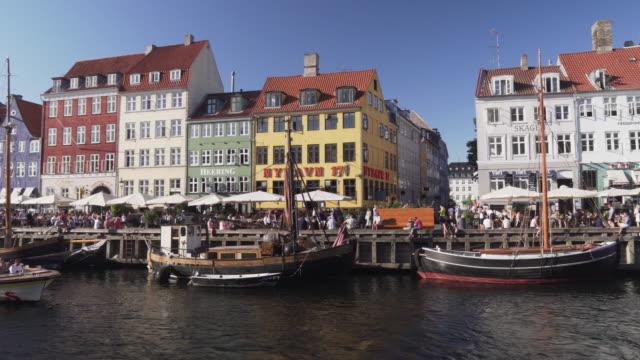 panorering visa: färgglada traditionella hus i köpenhamn nyhavn stad, folkmassor njuter restauranger barer, danmark - dansk kultur bildbanksvideor och videomaterial från bakom kulisserna