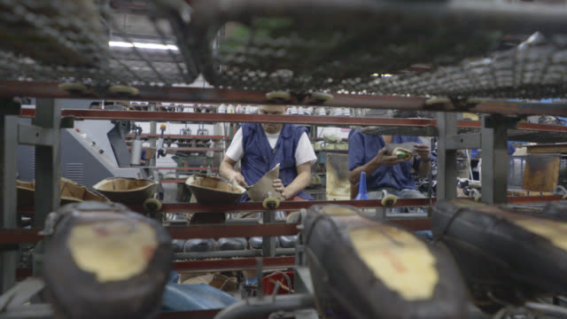 Panning view of operators working in a shoe factory video