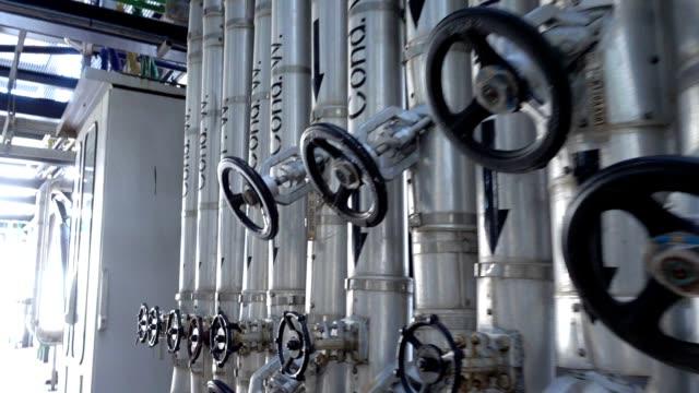 stockvideo's en b-roll-footage met panning mening van de metaalpijpleiding van de stoom met isolatie, gelabelde kokhalzen en kleppen in krachtcentrale - chemische fabriek