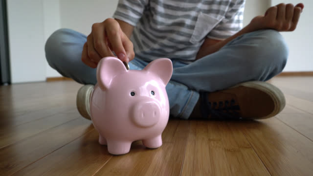 Panning view of unrecognizable child putting coins into a piggybank video