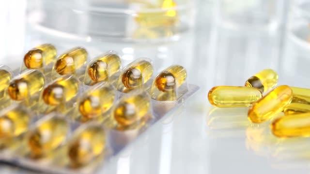 панорамирование витамины добавки таблетки omega 3 on table isolated - vitamin d стоковые видео и кадры b-roll