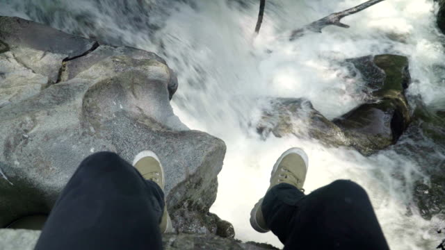 panning: Young brave man siting on high cliff above the waterfall video
