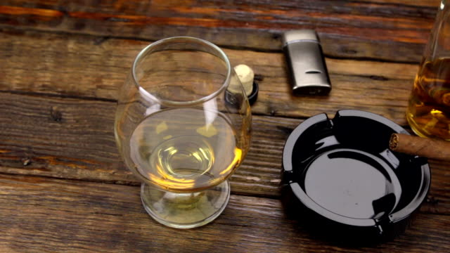panorama. a cigar in an ashtray and a glass of alcohol are on the old table. - sigaro video stock e b–roll