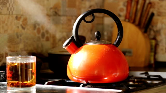 panorama lungo il kettle che possa sul fornello a gas. - bollente video stock e b–roll