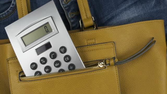 Panorama. La calculatrice sort d'une poche du sac d'une femme. Vue supérieure. - Vidéo