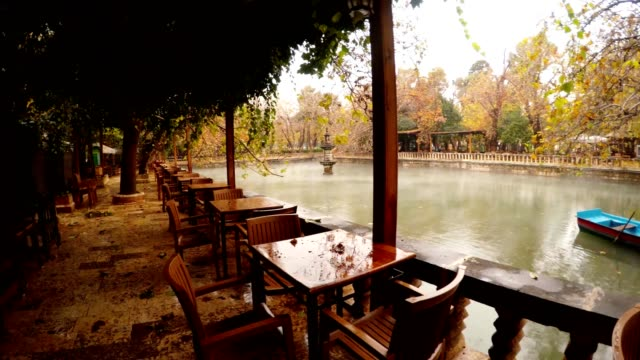 Panorama Empty Restaurant Two Blue Boats Moor Fog Floats under Lake Ayn-Zelih around Green and Yellow Trees Park Urfa video