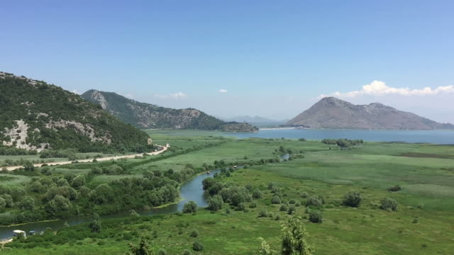 Panorama of a wonderful landscape. Green valley blue sky, blue mountains, small river lake. Aerial view of beautiful nature. Relaxing spectacle. Great background. video