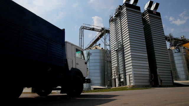 panorama of grain trucks driving to unload at silo on elevating hydraulic platform unloader. grain crops transshipment at big sea terminal at seaport. logictics concept. unloading grain at silo. - личный аксессуар стоковые видео и кадры b-roll
