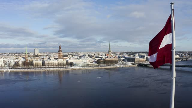 vídeos de stock e filmes b-roll de panorama of riga city with a big latvian flag in the foreground during beautiful sunny winter day. magical old town of riga in the background. latvian flag. - letónia