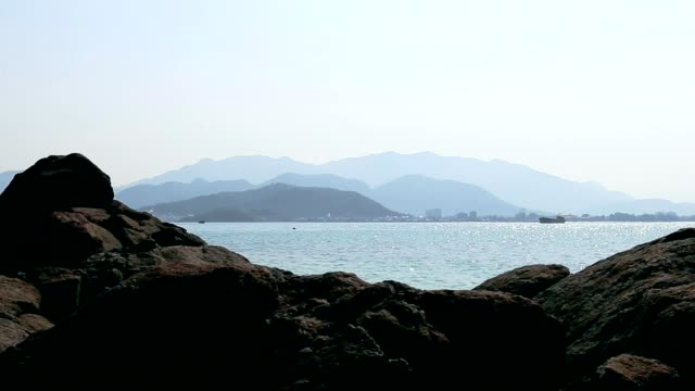Panorama of seascape with stones blue ocean and skyline sity. video