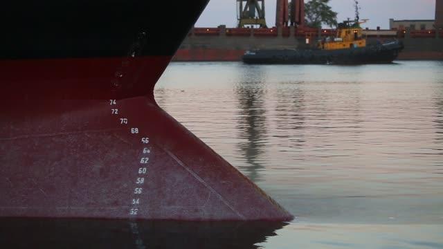 panorama över nedsänkt i vatten fraktfartyg fören på fartyget under last vikt. utkast till märken på ett bulkfartyg - vattenlinjen nummer på fören och aktern av ett fartyg på seaport på kvällen - skrov bildbanksvideor och videomaterial från bakom kulisserna