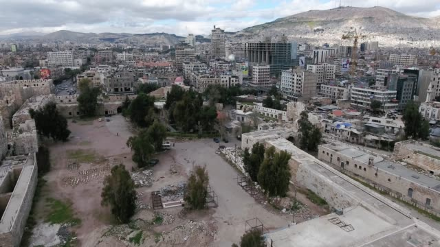 Panorama of the city of Damascus in Syria under cloudy sky. We ca see the ancient city through the horizon - aerial view with a drone Aerial view of the city of Damascus in Syria under cloudy sky. We ca see the ancient city through the horizon. Th city is damaged after civil wars, we can see ruins around the streets damascus stock videos & royalty-free footage