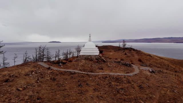 vídeos de stock e filmes b-roll de panorama of the island of ogoy in cloudy weather. buddhist stupa on lake baikal. - irkutsk