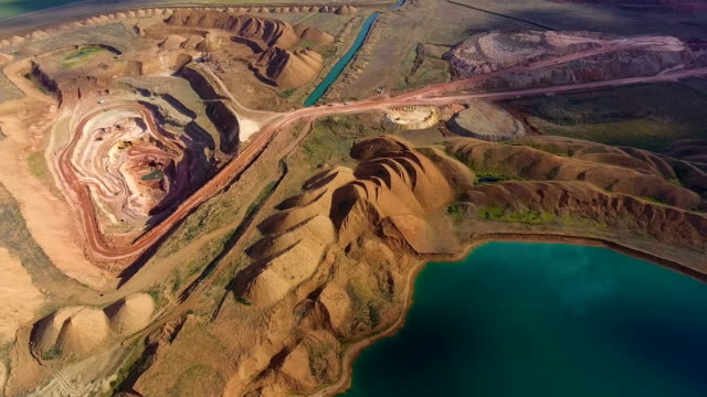 Panorama of the quarry. Artificial lake. Sunset. Horizon. Development of minerals. Aerial view of opencast mining quarry with lots of machinery at work - view from above. Bauxite mine. Ore handling. Excavators draw ore. Dump trucks carry ore. Azure water. Video footage from the drone. kazakhstan stock videos & royalty-free footage