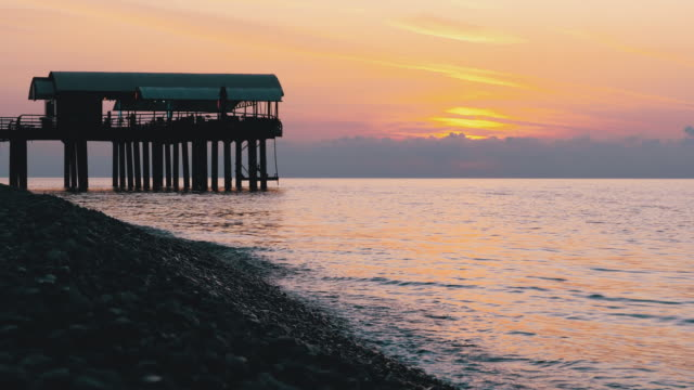 Panorama of the Sunset over the Sea next to the Silhouette of the Pier