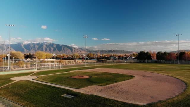 vidéos et rushes de panoramique aérienne drone shot d'un drapeau américain ondulant dans la brise, vider le domaine/terrain de baseball, les montagnes wasatch et salt lake city au lever/coucher du soleil - baseball