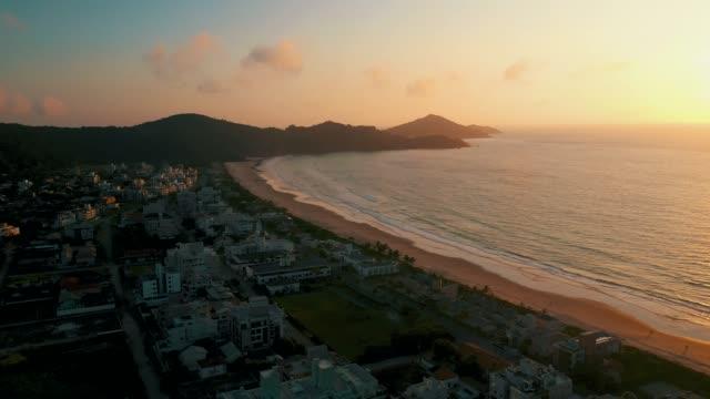 vídeos de stock, filmes e b-roll de panorâmica aérea litoral praia da cidade do sol - sol nascente horizonte drone cidade