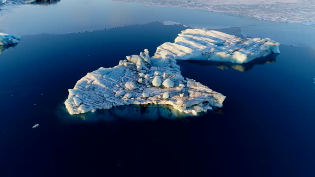 panoramic aerial view of a landscape of white icebergs and a glacier in iceland. there is only white ice and snow on the sea in the horizon, under the sunset. - ghiaccio galleggiante video stock e b–roll
