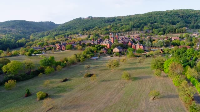 Panoramic aerial view of the village of Collonges-La-Rouge in France. The village is in the middle of a forest and green fields.
