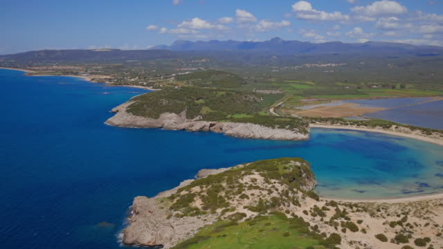 panoramic aerial view of voidokilia beach ( ox stomach bay or ochsenbauchbucht ) - bay of ionian sea near pylos - messenia - peloponnese region of greece - пелопоннес стоковые видео и кадры b-roll