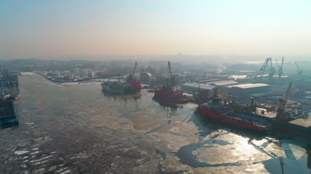 panoramic aerial view on the industrial port with commercial ships and cargo containers in winter. - acqua ghiacciata video stock e b–roll
