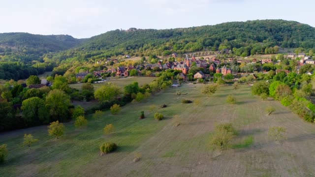 Panoramic aerial view with a drone of the village of Collonges-La-Rouge in France. The village is in the middle of a forest and green fields.
