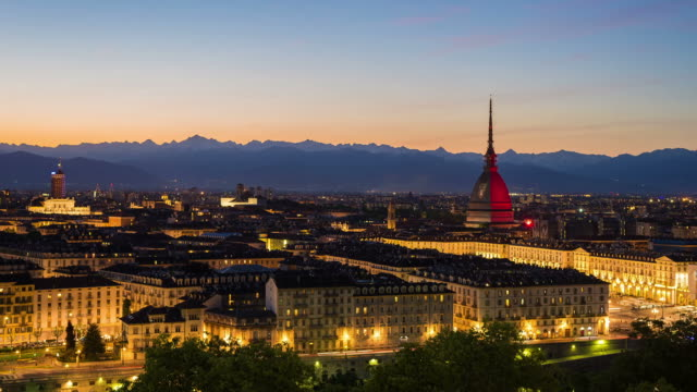 Torino, Italy - May 4, 2016: panoramic cityscape fading from sunset to night. Mole Antonelliana glowing with Torino FC colors in memory of the 1949 Superga airplane crash, carrying the entire Torino FC team. video