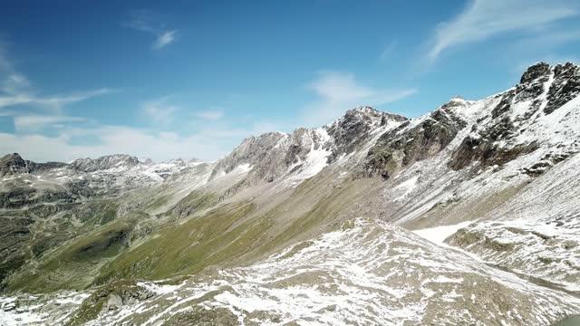 un drone panoramico ha colpito pendii nella regione di hohe tauern in austria. le piste sono parzialmente coperte di neve. parti superiori ripide e taglienti. c'è un lago alpino in fondo. serenità - stato federato del tirolo video stock e b–roll