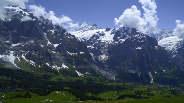 panorama panorering shot-berg i blå himmel första grindelwald schweiz - grindelwald bildbanksvideor och videomaterial från bakom kulisserna