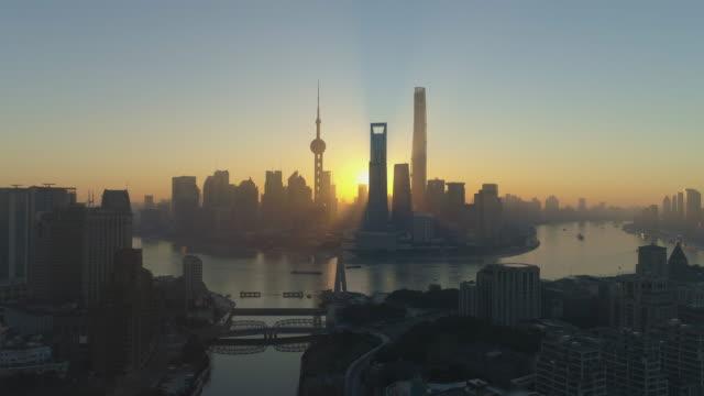 Panoramic Shanghai Skyline and Waibaidu Bridge at Sunrise. Lujiazui Financial District and Huangpu River. China. Aerial View. Drone is Flying Backward and Upward. Establishing Shot.