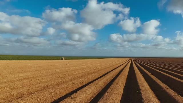 Panoramic Time lapse of furrowed agricultural fields prepared for planting crops and vegetables in Normandy, France. video