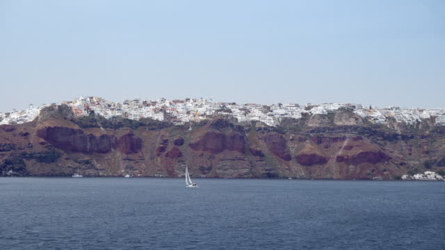 panoramic view from sea to santorini caldera and iconic architecture of fira town - isole egee video stock e b–roll