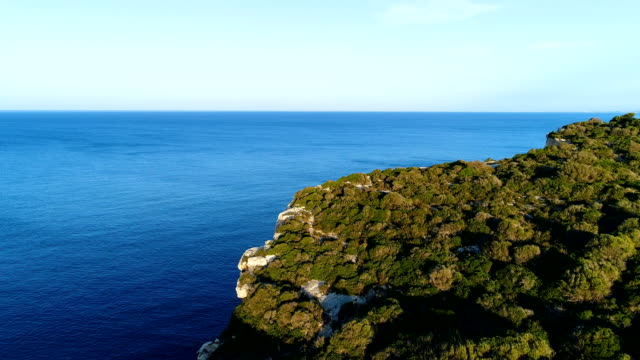 panoramic view of a cliff in mediterranean sea, with the reflection of the sun in blue water sea. there is only grass and rocks on the cliff, with the sea in the horizon in minorca, spain. - горизонт над поверхностью воды стоковые видео и кадры b-roll
