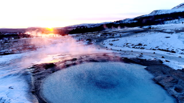 Panoramic view of a geyser in Geysir, Iceland. Smoke is getting out of the geyser with people walking all around the geyser, under the red and orange sunset.