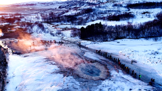 vídeos de stock e filmes b-roll de panoramic view of a geyser in geysir, iceland. smoke is getting out of the geyser with people walking all around the geyser, under the red sunset. - geologia