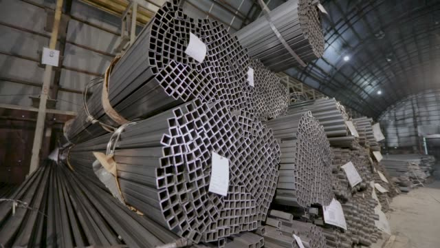 Panoramic view of a large warehouse with metal. Profile pipe in a covered warehouse, profile pipe laid in rows in a large warehouse, warehouse with metal Square profile pipe, metal warehouse. Clean, metal warehouse, metal profile stacked in rows. Close-up, panorama durability stock videos & royalty-free footage