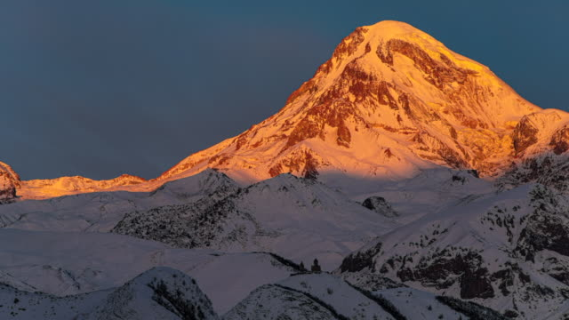 stockvideo's en b-roll-footage met panoramisch uitzicht op de kaukasus bergen, gergeti trinity church tsminda sameba en zonlicht in een ochtend, mijlpaal van georgië - sneeuwkap
