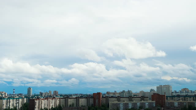 Panoramic view of city background blue sky with floating clouds. Concept. Wide sky with overcast clouds floating over houses of large city