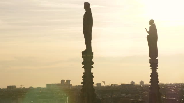 panoramic view of milan from roof of the cathedral rooftop. statues and sculptures on duomo di milano at sunset. italy. - incisione oggetto creato dall'uomo video stock e b–roll
