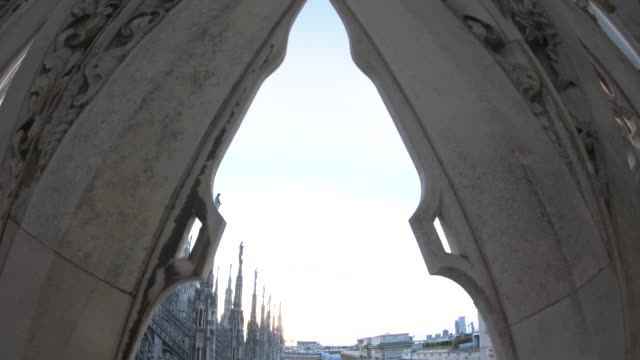 Panoramic view of Milan from roof of the cathedral rooftop. Statues and sculptures on Duomo di Milano at sunset. Italy.