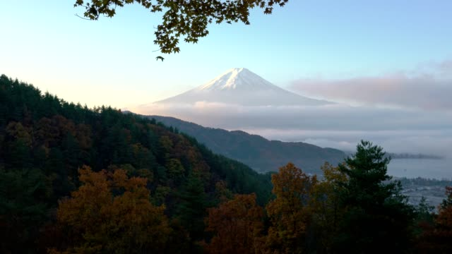 Panoramic view of Mount Fuji with sea of mist and red maple leaves in the autumn morning video