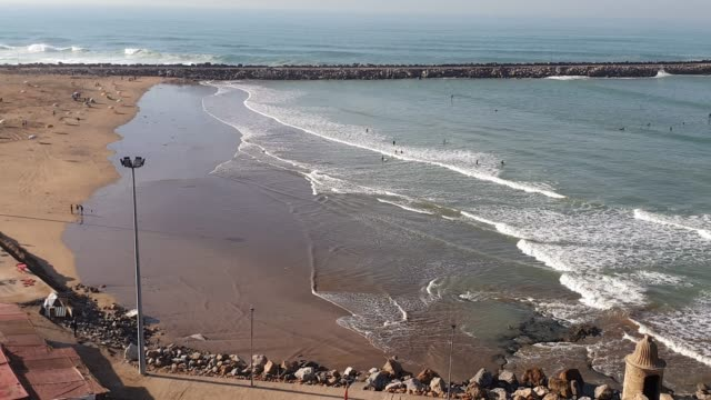 Panoramic view of Rabat's beach from Kasbah of the Udayas. Many people is surfing on the waves of the bay
