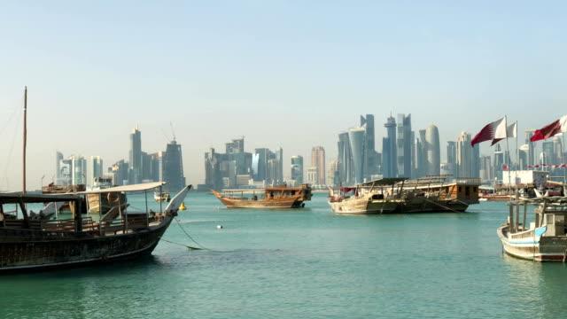 vidéos et rushes de une vue panoramique sur le vieux port à doha, au qatar, avec la skyline de west bay en arrière-plan. gratte-ciel modernes sur le fond et de vieux bateaux traditionnels sur le premier plan. - doha
