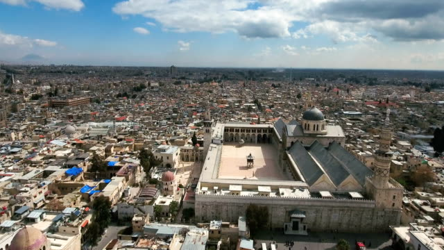 vídeos de stock e filmes b-roll de panoramic view of the umayyad mosque in syria. drone is flying over the city of damascus to the religious mosque. - síria