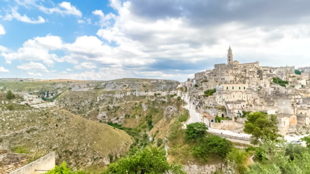 panoramic view of typical stones (Sassi di Matera) and church of Matera UNESCO European Capital of Culture 2019 under blue sky white clouds time lapse movement, Basilicata - video