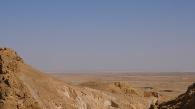 Panoramic view on Atlas Mountains and desert valley in Sahara near Oasis Chebika. Panning shot Panoramic view on Atlas Mountains and desert valley in Sahara. Mountains in sandy desert near Oasis Chebika in Tunisia canyon stock videos & royalty-free footage