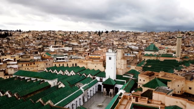 Panoramic view over the medina of Fez in Morocco under a cloudy sky. In the foreground, we can see the rooftops of the university of Al Quaraouiyine.