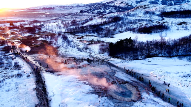 panoramic view with a drone of a geyser in geysir, iceland. smoke is getting out of the geyser with people walking all around the geyser, under the red sunset. - ice on fire video stock e b–roll