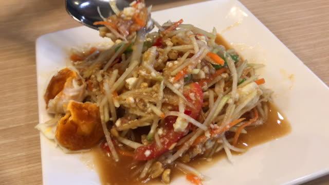 vidéos et rushes de salade de papaye accompagnée de plats thaïs traditionnels. - apprivoisé